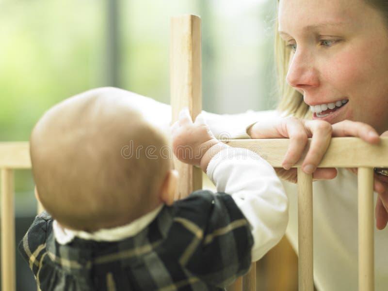 Mamma, die am Schätzchen über Playpen-Geländer lächelt lizenzfreie stockfotografie