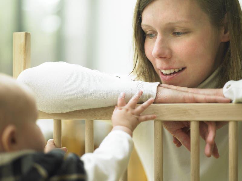 Mamma, die am Schätzchen über Playpen-Geländer lächelt stockfoto