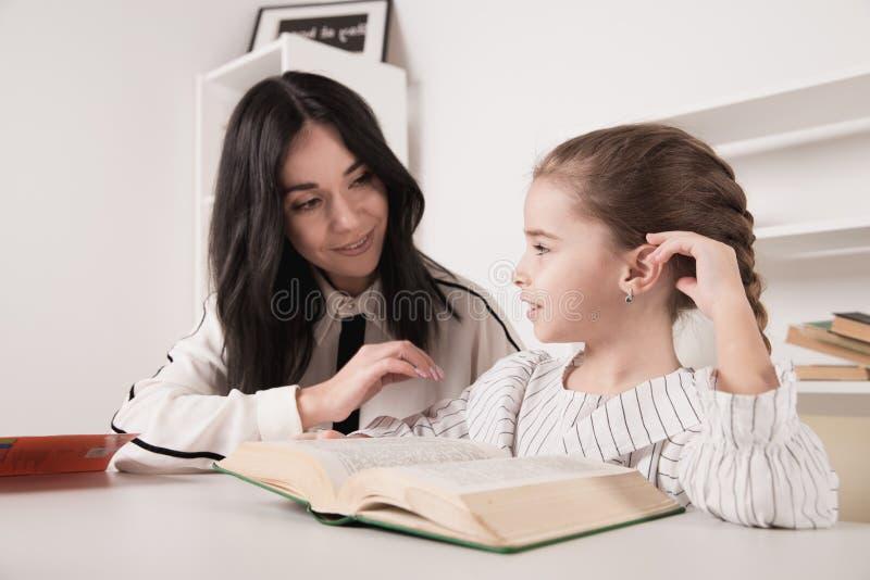 Mamma die thuiswerk met dochter doen en boek lezen royalty-vrije stock foto's