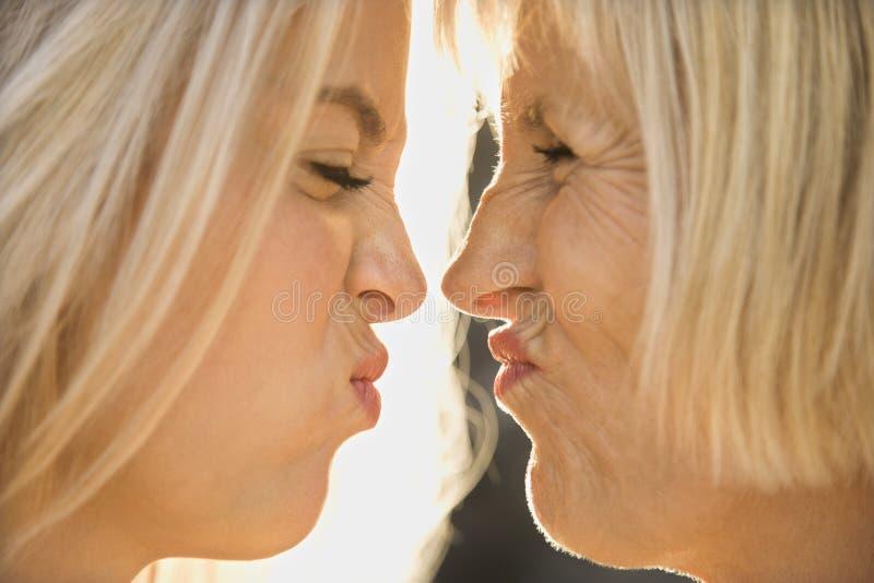 Mamma e figlia che fanno i fronti. fotografia stock