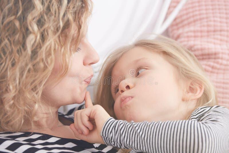 Mamma e figlia che fanno i fronti immagine stock