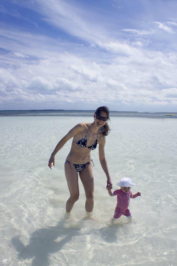 Mamma e figlia che giocano in acqua immagine stock libera da diritti