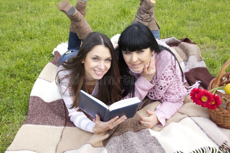 Mamma e figlia che leggono un libro immagini stock libere da diritti