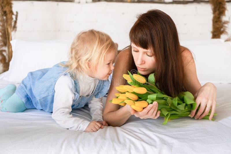 Mamma e figlia che si trovano insieme su un letto bianco con un grande mazzo dei tulipani gialli immagini stock libere da diritti