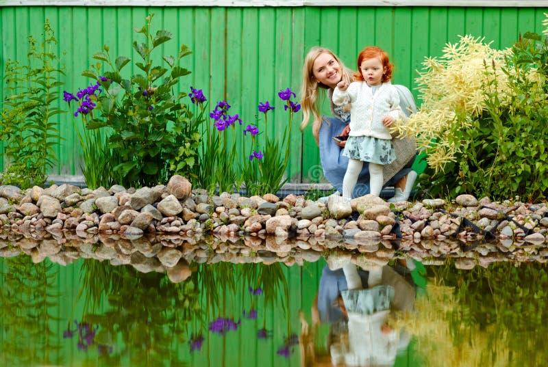 Mamma e figlia dai capelli rossi di estate nel parco al pon fotografia stock