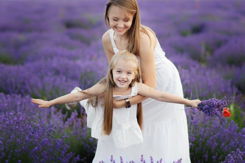Mamma e figlia nel giacimento della lavanda Concetto di amore della famiglia Mosca della bambina in mani delle madri fotografia stock