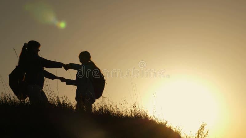 Mamma e figlia sulla vacanza che viaggia e che balla sulla montagna Donna con le mani sollevate sopra la montagna che esamina fotografia stock