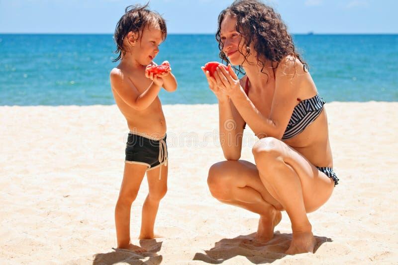 Mamma e figlio che mangiano anguria fotografia stock