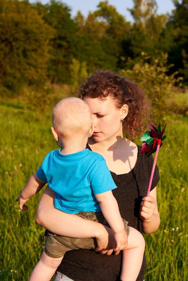 Mamma e figlio divertendosi in natura di estate, madre che tiene il suo bambino con la girandola fotografia stock libera da diritti