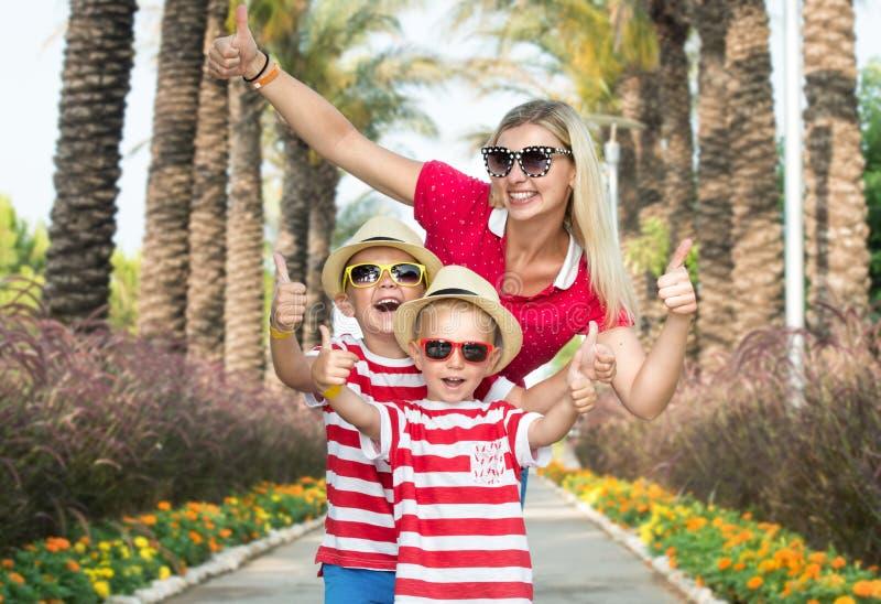 Mamma e figlio due in occhiali da sole e cappelli da camminare tramite il vicolo delle palme Vacanze estive della famiglia immagine stock