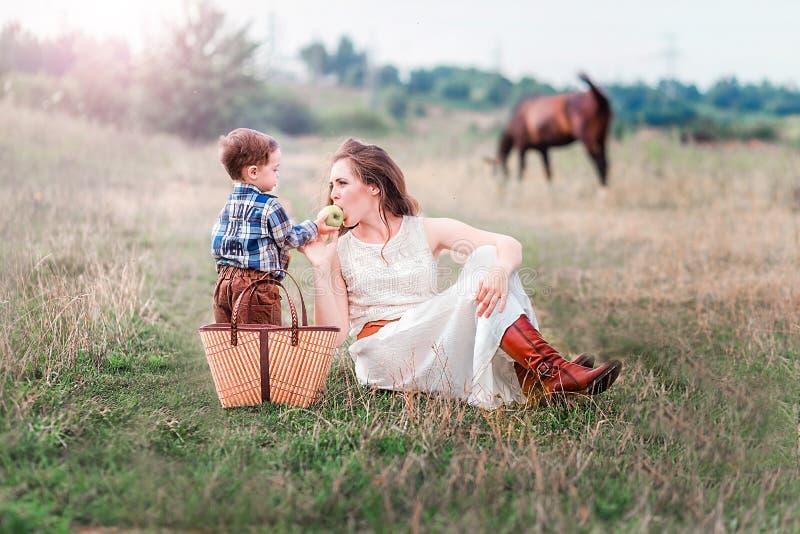 Mamma e figlio insieme su un picnic nel campo Cavallo nei precedenti fotografia stock