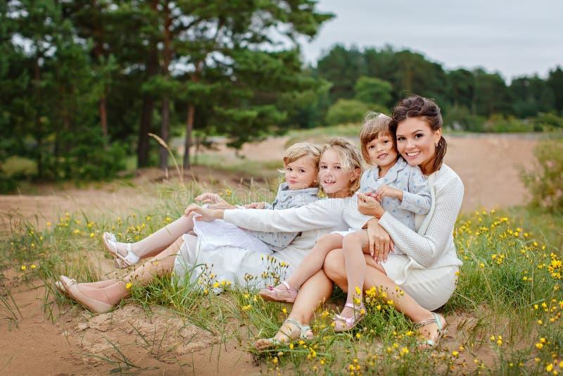 Mamma e le sue tre figlie che abbracciano in una foresta di estate immagini stock