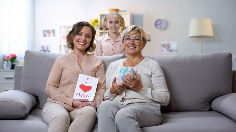 Mamma e nonna con i presente che si siedono sul sofà, condizione della figlia dietro l'8 marzo immagine stock libera da diritti