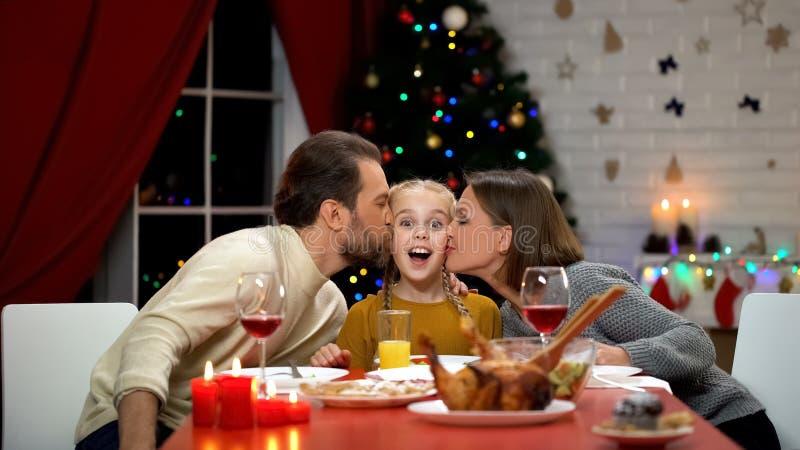 Mamma e papà che baciano figlia al pranzo di Natale, guardante alla macchina fotografica, vigilia di festa immagini stock