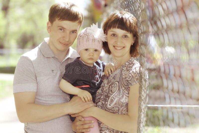 Mamma e papà con la piccola figlia in parco fotografie stock libere da diritti