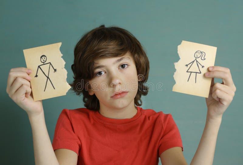 Mamma e papà della tenuta del ragazzo dell'adolescente che assorbono due pezzi di carta lacerati immagine stock