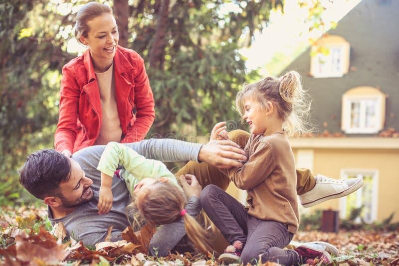 Mamma e sorelle che solleticano papà Allegro e divertimento immagini stock
