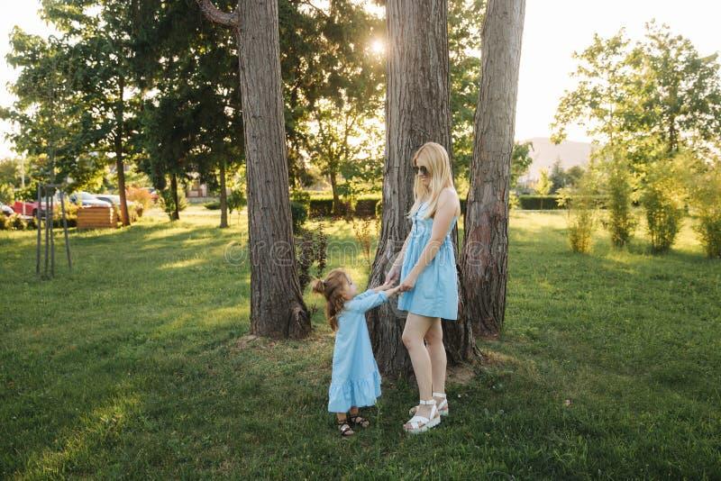 Mamma e sua figlia che camminano e che si tengono per mano fotografia stock libera da diritti