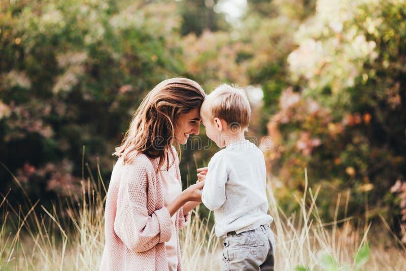 Mamma ed abbraccio e risata del figlio nel parco di autunno Spazio per testo immagini stock libere da diritti