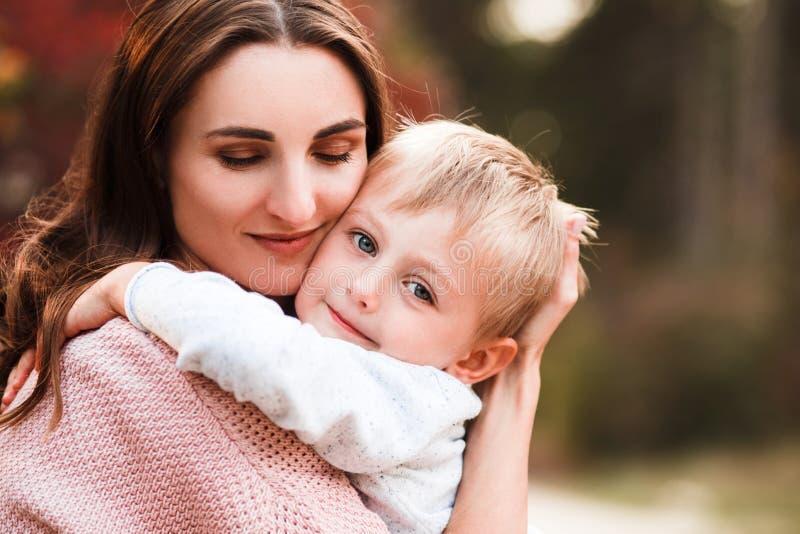 Mamma ed abbraccio e risata del figlio nel parco di autunno Spazio per testo fotografia stock libera da diritti