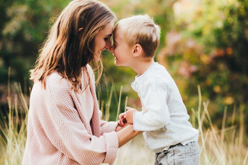Mamma ed abbraccio e risata del figlio nel parco di autunno Spazio per testo immagine stock