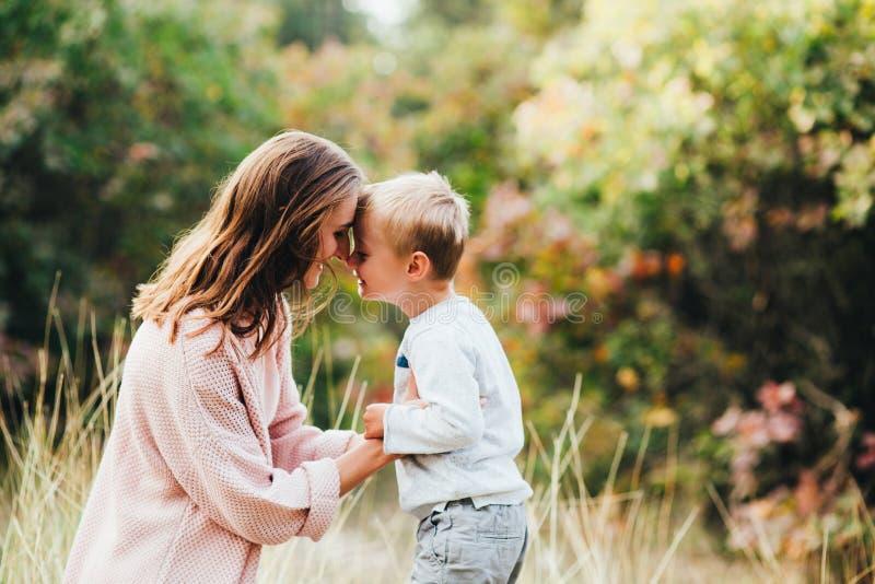 Mamma ed abbraccio e risata del figlio nel parco di autunno Spazio per testo immagini stock