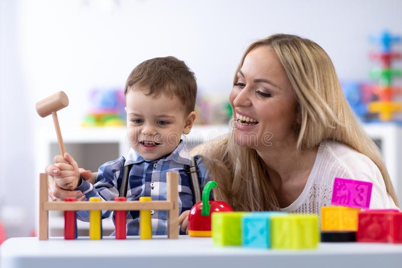 Mamma- eller lärareplayng med ungelilla barnet i barnkammare arkivfoton