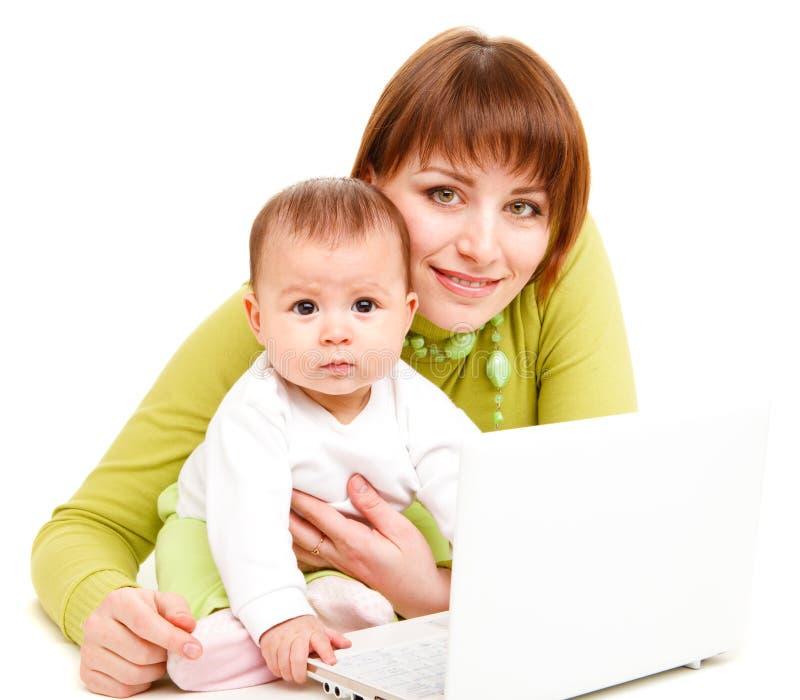 Mamma en baby die bij netbook werken royalty-vrije stock afbeeldingen