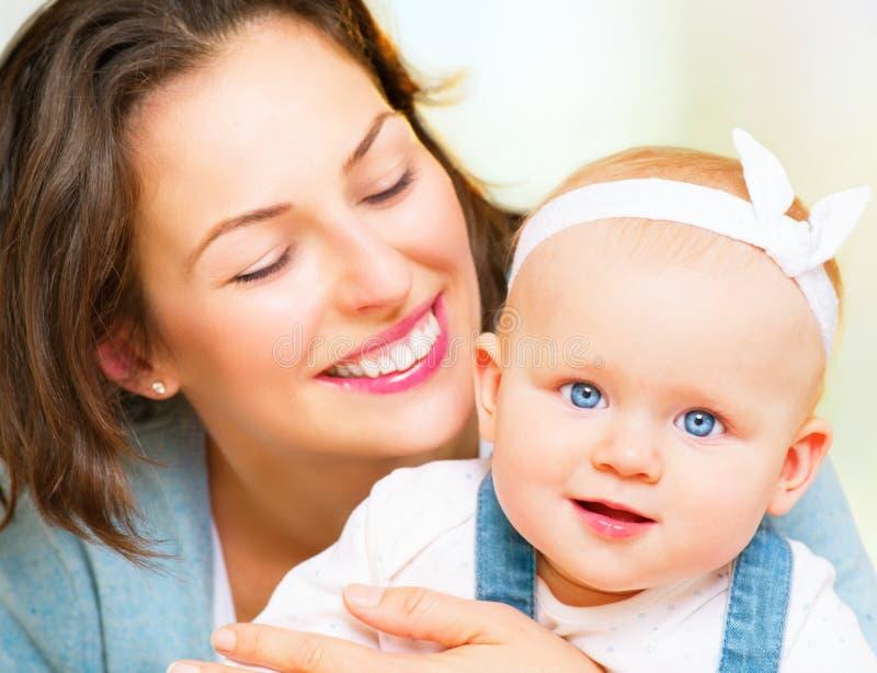 Mamma en baby en meisje die thuis kussen koesteren stock fotografie