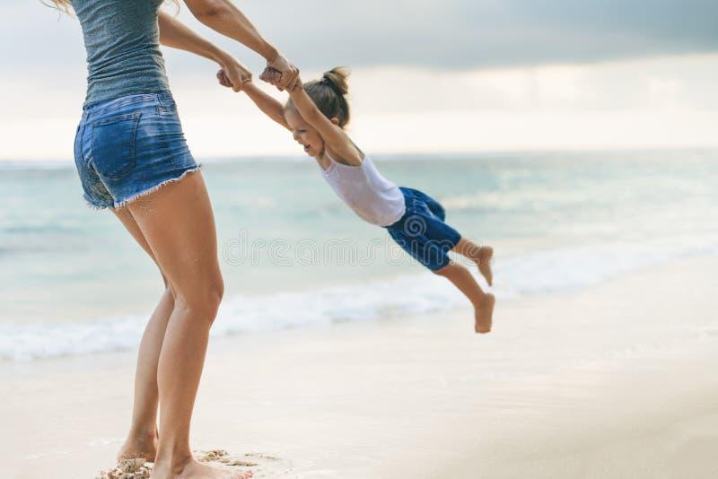 Mamma en baby het spelen dichtbij strand Reizend met familie, kind stock afbeelding
