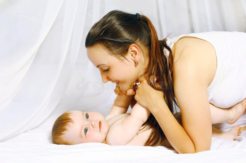 Mamma en baby het spelen in slaapkamer stock foto