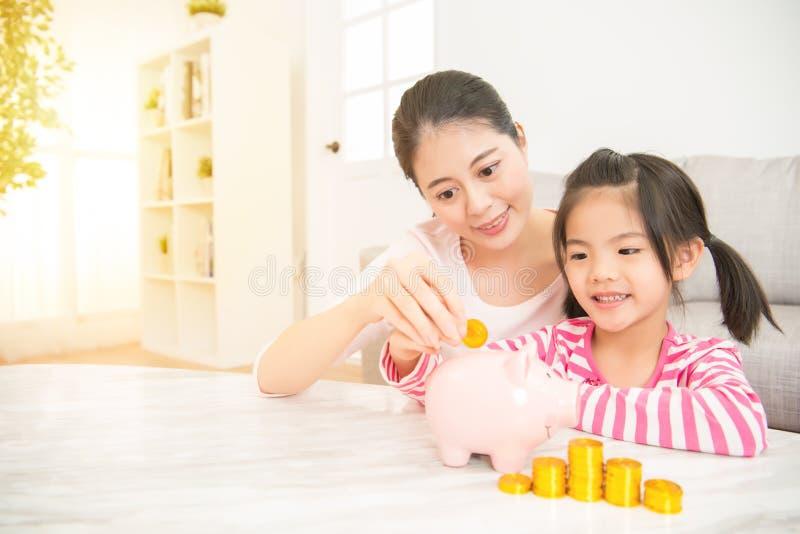 Mamma en dochter die muntstukken zetten in spaarvarken royalty-vrije stock foto