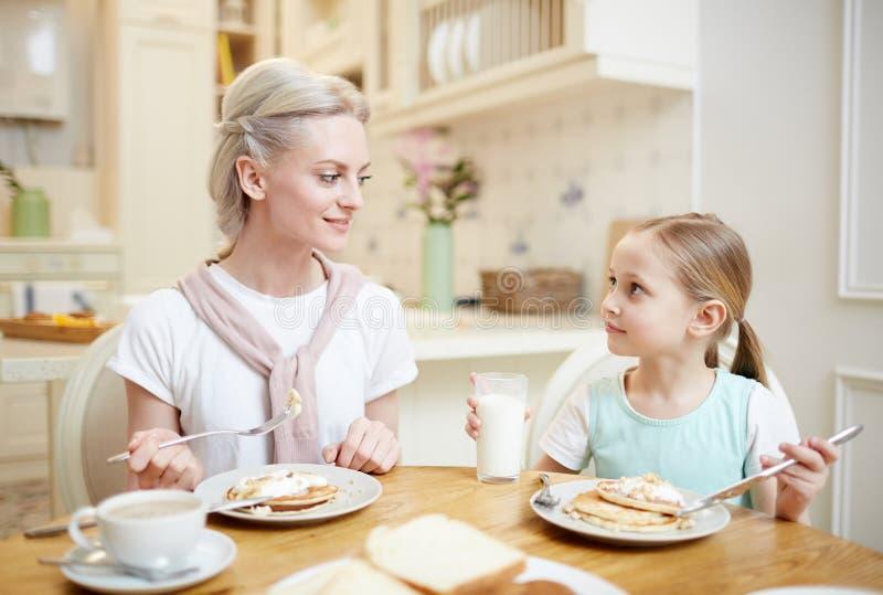 Mamma en dochter die pannekoeken en het spreken eten stock foto's