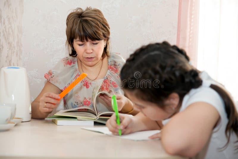 Mamma en dochter die thuiswerk doen stock foto's
