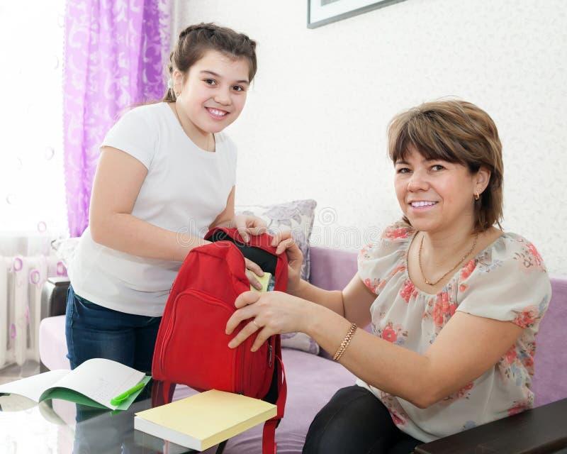 Mamma en dochter die thuiswerk thuis doen royalty-vrije stock afbeelding