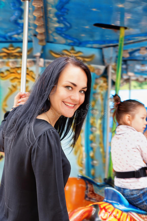 Mamma en dochter in het park en rit op de carrousel royalty-vrije stock fotografie