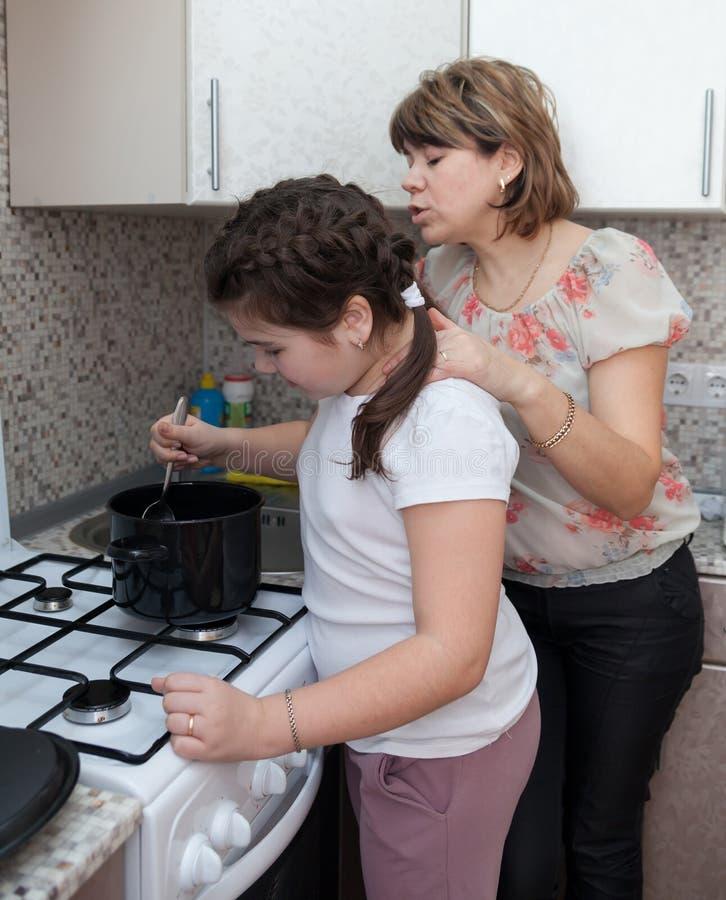 Mamma en dochter in het voorbereiden van soep stock foto's