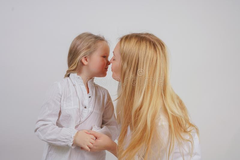Mamma en dochter in witte overhemden met het lange blondehaar stellen op een stevige achtergrond in de Studio de charmante famili royalty-vrije stock afbeeldingen