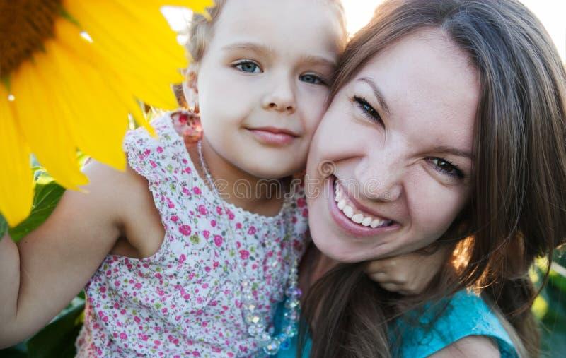 Mamma en dochter in zonnebloem stock fotografie