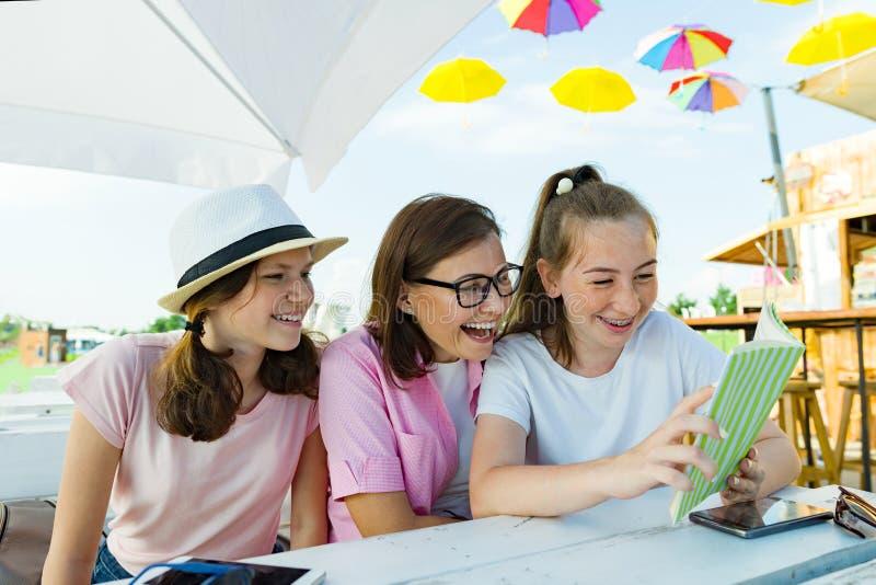 Mamma en dochters de tieners hebben pret, kijken en lezen grappig boek Mededeling van de ouder en de kinderen van adolescenten stock afbeeldingen
