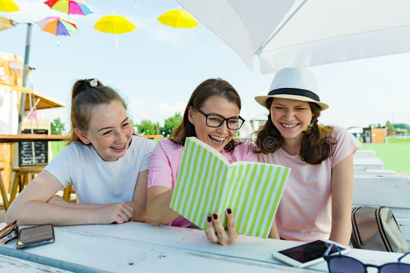 Mamma en dochters de tieners hebben pret, kijken en lezen grappig boek Mededeling van de ouder en de kinderen van adolescenten royalty-vrije stock afbeelding