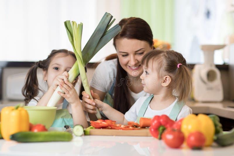 Mamma en jonge geitjes de dochters hebben een pret voorbereidend groenten in een keuken van het familiehuis stock foto