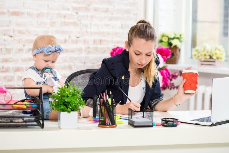 Mamma en onderneemster die met laptop computer werken thuis en met haar babymeisje spelen royalty-vrije stock foto's