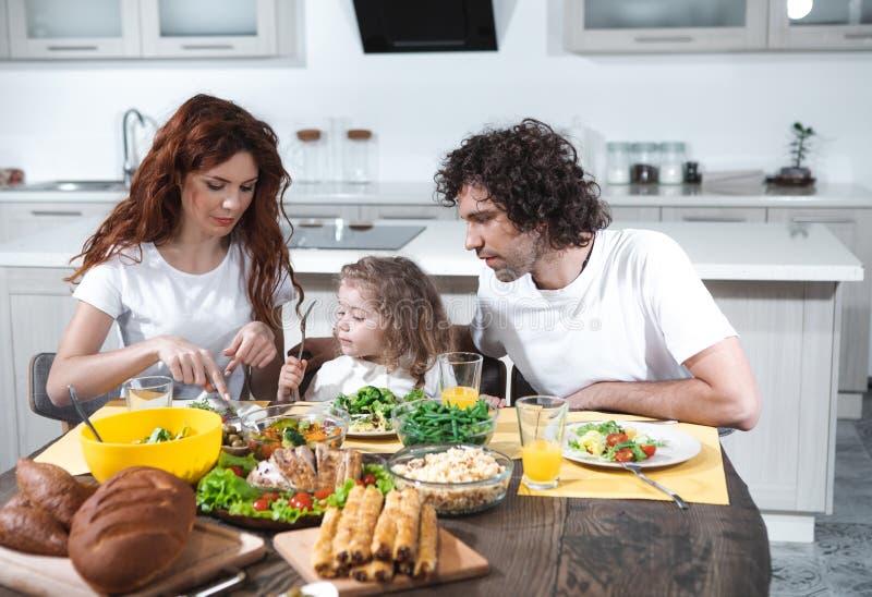 Mamma en papa die weinig dochter in keuken voeden royalty-vrije stock fotografie