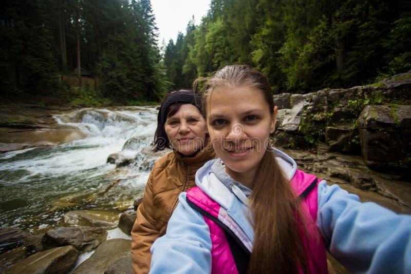 Mamma en volwassen dochterzitting in het bos dichtbij de rivier en het nemen selfie stock foto's