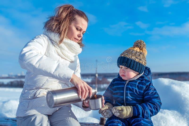 Mamma en weinig de jaar van jongenszoon 3-4 oude straat van de bankwinter, sneeuwsneeuwbanken op achtergrond Giet in een mok Ther royalty-vrije stock foto's