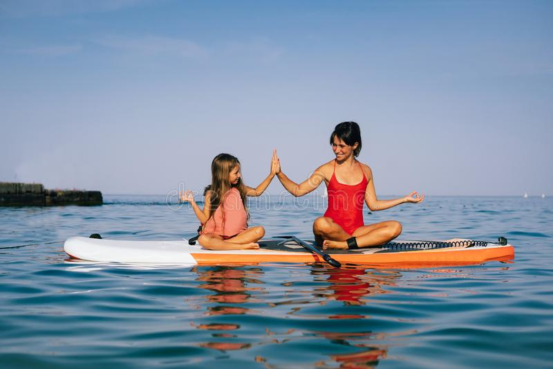 Mamma en weinig dochter die yoga op de peddelraad doen royalty-vrije stock fotografie