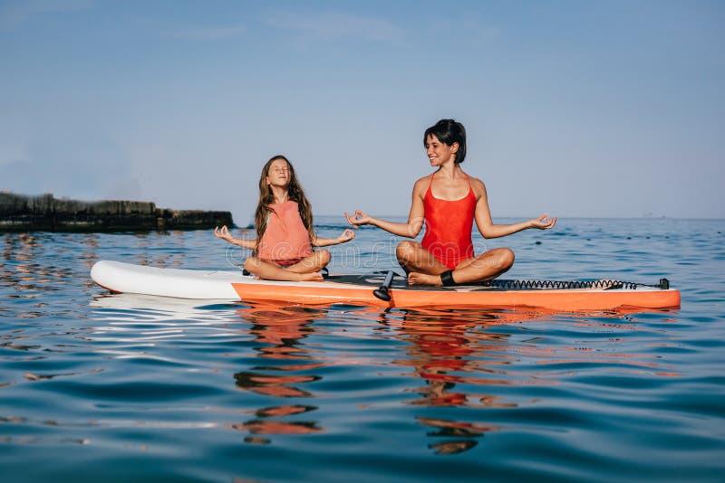 Mamma en weinig dochter die yoga op de peddelraad doen stock fotografie