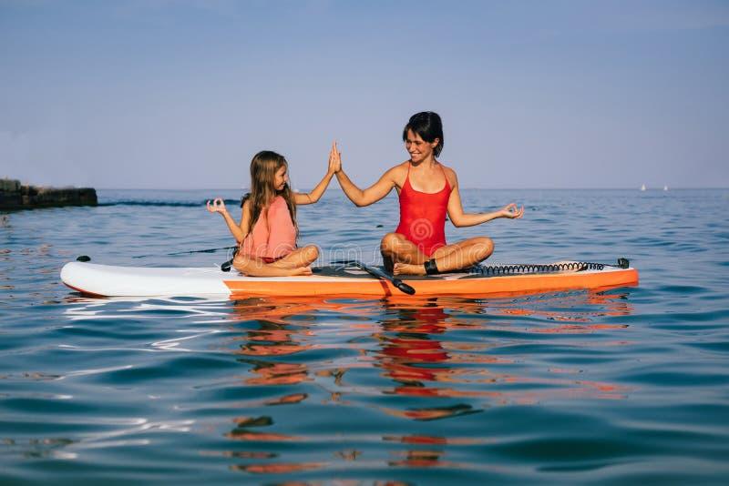 Mamma en weinig dochter die yoga op de peddelraad doen stock afbeeldingen