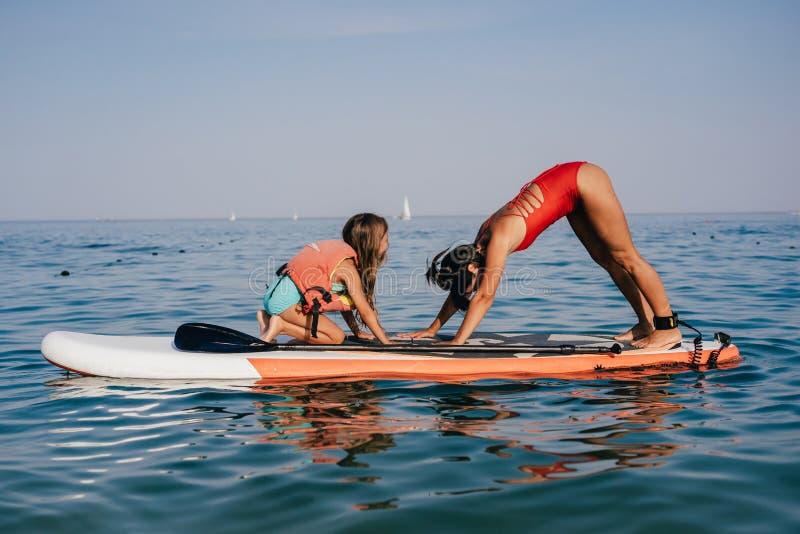 Mamma en weinig dochter die yoga op de peddelraad doen royalty-vrije stock afbeeldingen